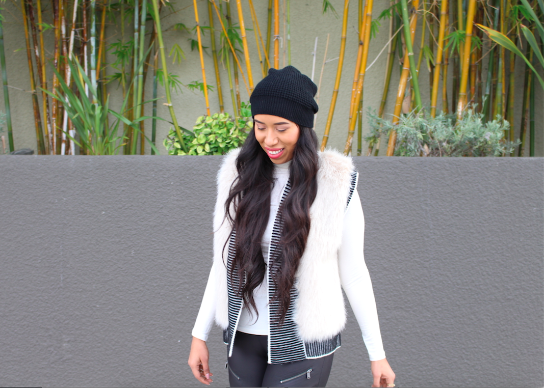 How to Style a Faux Fur Vest - A fluffy vest, or how it is most commonly known as--faux fur vest, has become a staple piece in my wardrobe. I love these type of vests so much since they can be used all year round either for casual or dressy occasions, and they keep you looking trendy. Fluffy vests are very eye-catching, so they look best when worn with simple items. Solid colored leggings and denim jeans (without tears) are ideal pairings for a faux fur vest. It keeps the attention on your vest. Keeping this rule in mind makes for a balanced outfit. Now when it comes to dresses the rules do change a little, prints are welcomed, a flowy silhouette works best, pleats are a plus, and over the knee boots are a must.