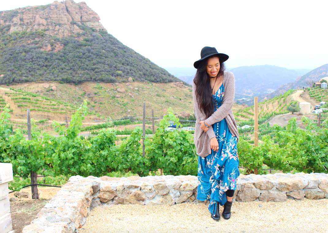 Can you believe I've never been wine tasting before? Almost everyone I know has done it at least once in their lifetime. So when I had the chance to try out Malibu Wine Safari, a safari tour that also includes wine tasting, I jumped at the opportunity right away. I wanted to wear something really comfortable to the tour, since I knew I was going to be getting on and off a truck for an hour. At the same time though I also wanted to look stylish, so I opted for a beautifully printed botanical button down maxi dress. The ruffle trimmed neckline really gives off a romantic flare. It also comes in yellow, however I liked the blue a little more on me. The fit is very fitted through out the body, making it the perfect dress to show off your figure. Since it was really cold I paired it with a slouchy cardigan and believe it or not, sweat pants underneath! lol My squared heel booties came in handy on this day. I was having a really bad hair day due to the humidity in the air, so my cute black hat saved the day. I finished my look by tying a black little string around my neck as a choker. I felt right on trend.
